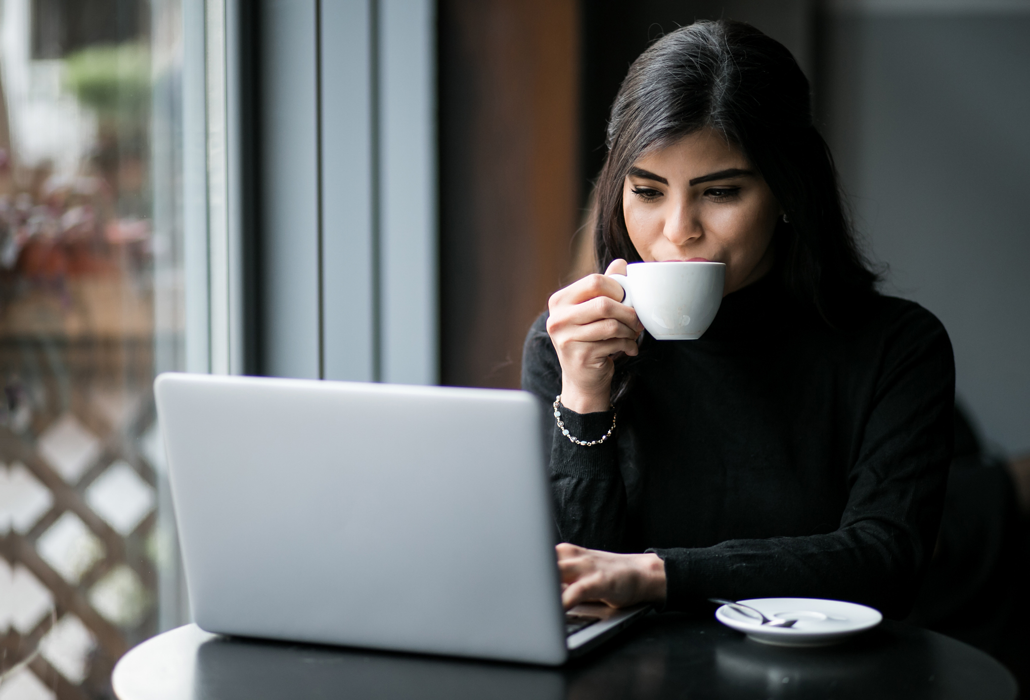Woman working at computer in coffee shop.